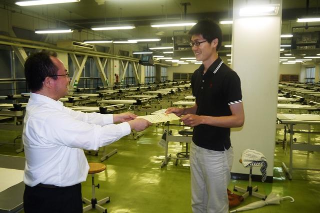 対策講座を受講した製図室で、合格証書を受け取る石井君。