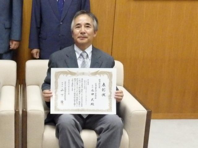7月13日に中国電力(株)で行われた授賞式で表彰状を手にする永田教授