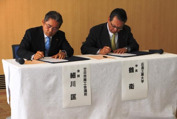協定書に署名する細川会頭(左)と鶴学長(右)