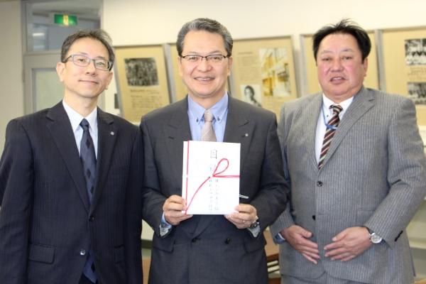 目録を手にする鶴学長(中)と、株式会社木下組の田中様(右)、中国銀行の大森様(左)