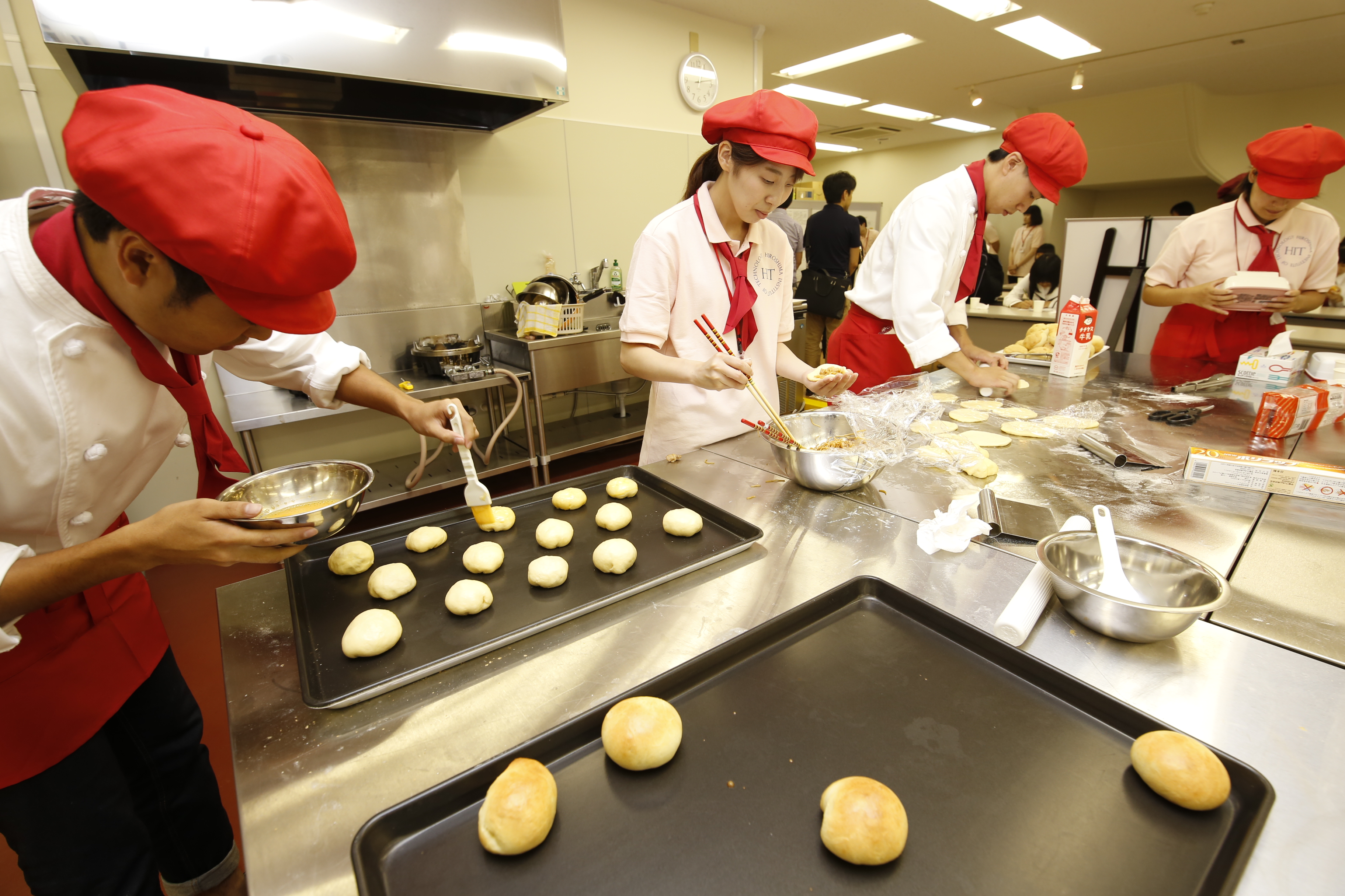 食品実験棟では、業務用オーブンを使用して発酵食品の一つである「パン」を学生が実演製作。酵母の働きや食品製造設備について理解を深めることができます。(食品生命科学科)