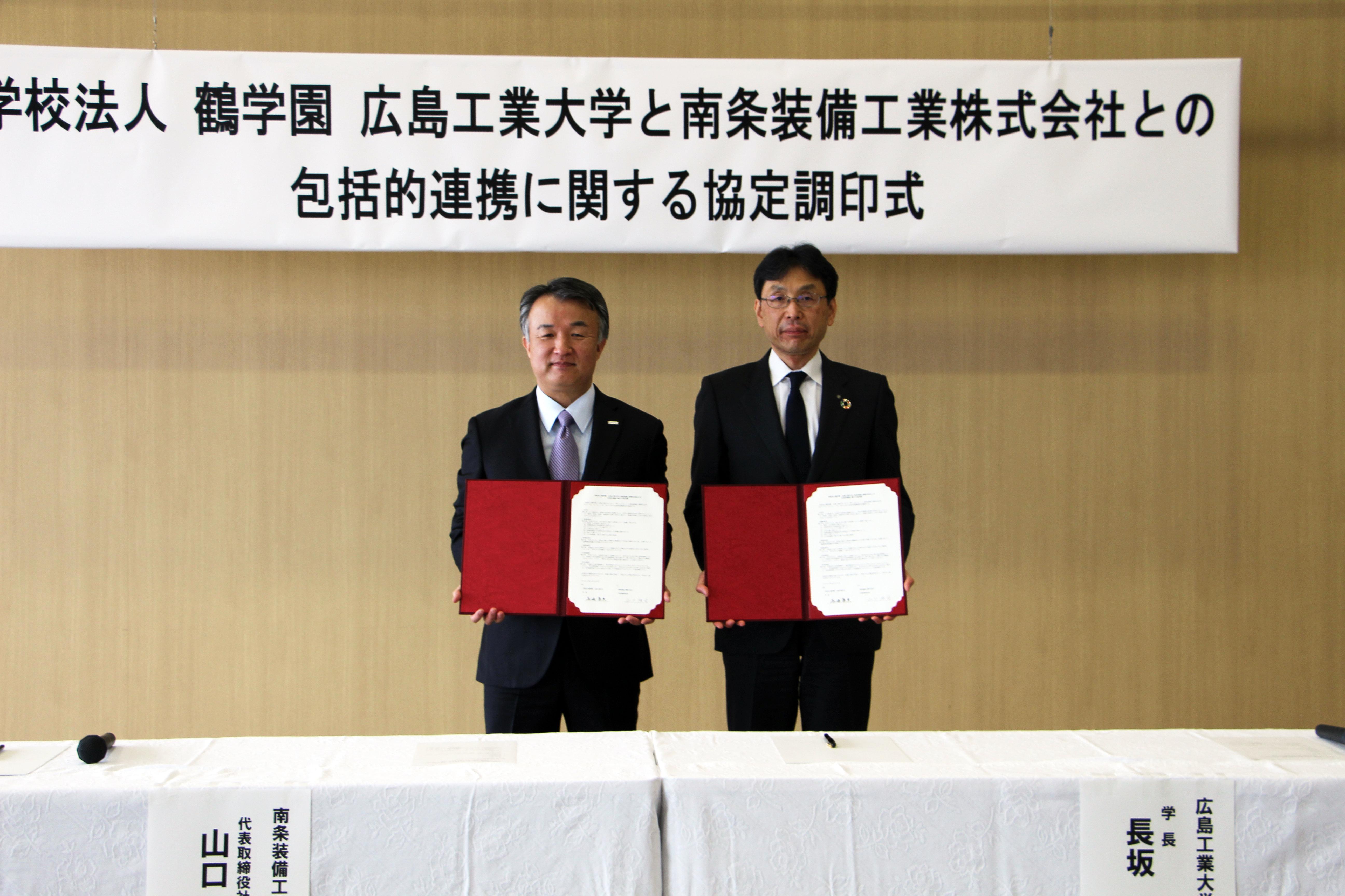 協定書を掲げる山口社長と長坂学長