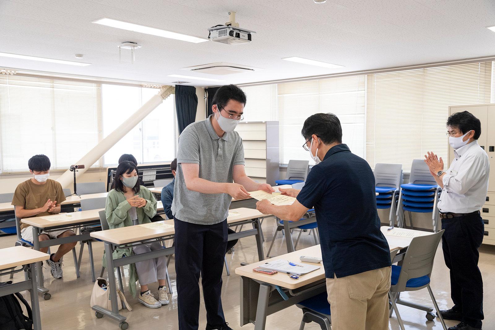 検定3級の資格を取得した学生に、日吉先生から合格証書と記念品が手渡されました。
