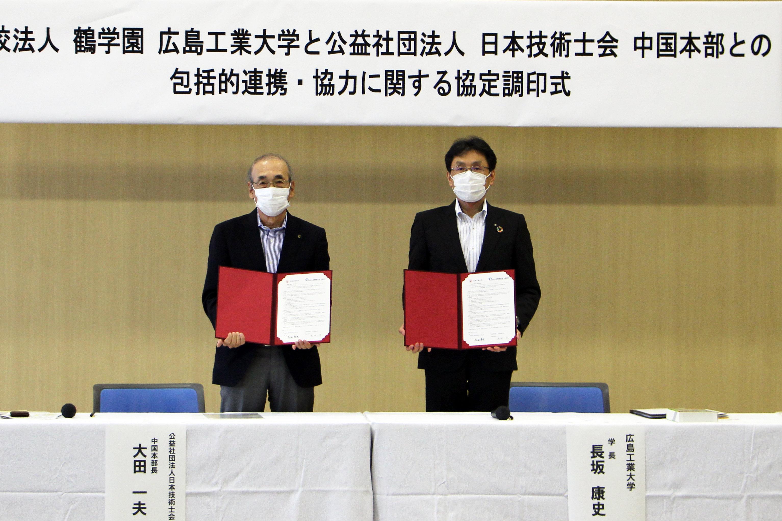 協定書を掲げる大田中国本部長と長坂学長