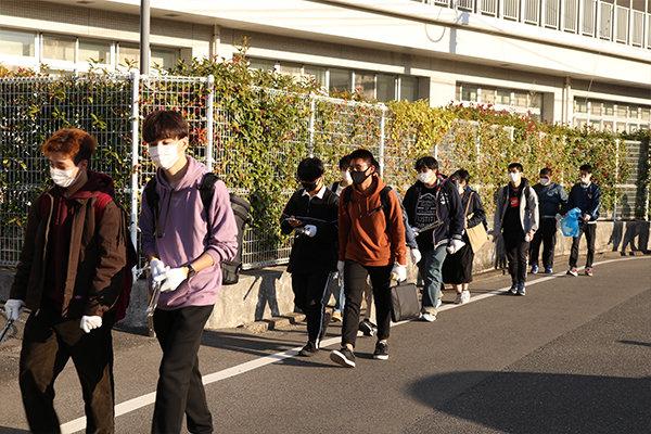 大学周辺の清掃に向かう学生