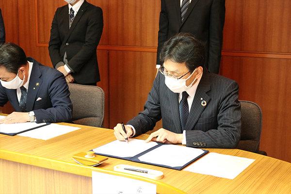 協定書に署名する長坂学長