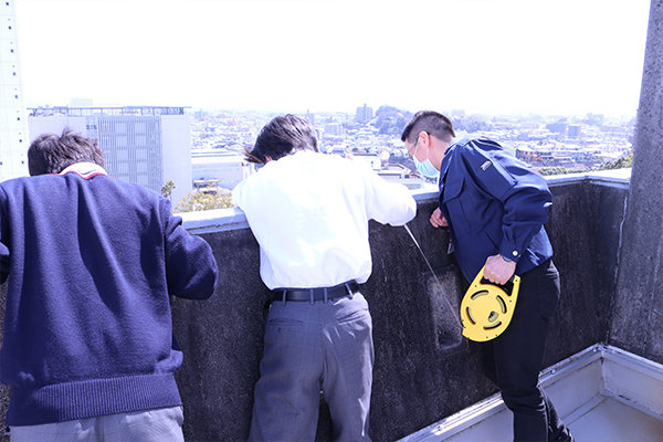 メジャーを地上に下ろし、5号館の高さを測定