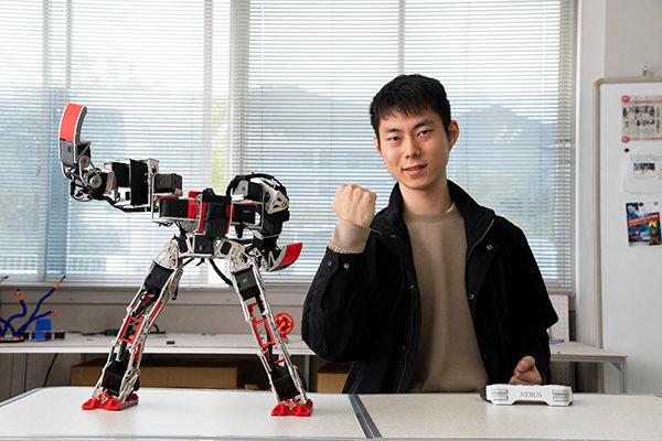 美しくポージングする二足歩行ロボット「NEXUS」と同じポーズで喜びを表現する、ロボット研究部部長・尾田 俊祐さん