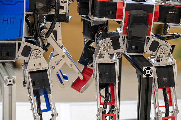 「1世代前(左の青)のロボットと比較すると、例えば足の付根部分を細い枠の構造に変更して軽量化しました。これでも強度が保てることは確認済みです」と尾田さん。細部に工夫がつまっています。