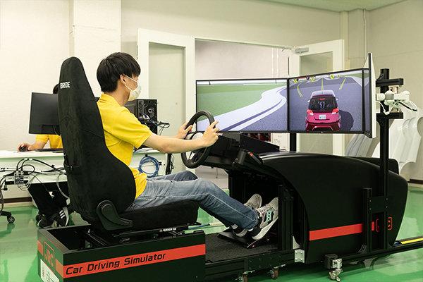 自動運転シミュレータ。ハンドルを離すと、人に代わってシステムが車を操ります