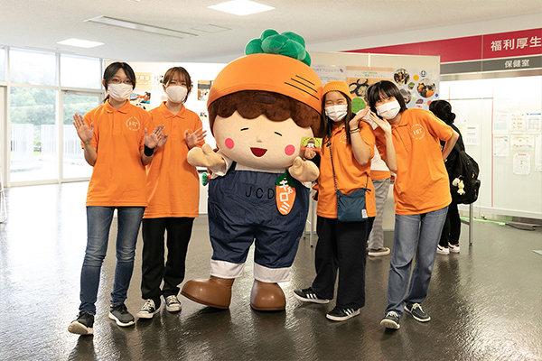 女子学生が主体となって運営するJCDセンターのメンバーと、JCDマスコットキャラクターのキャロミ
