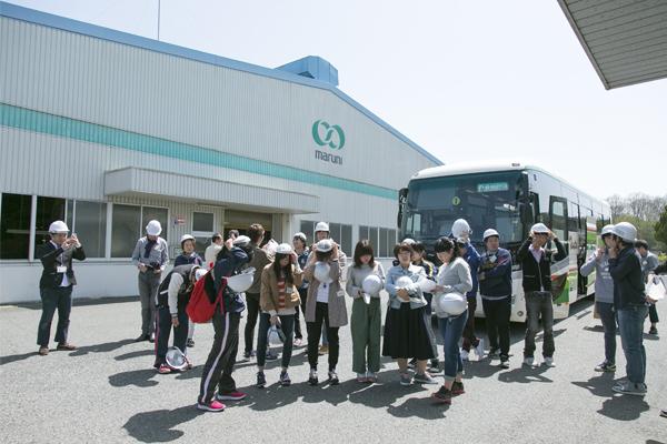 バスに乗って、マルニ木工に到着。工場内はヘルメットを着用して見学します。