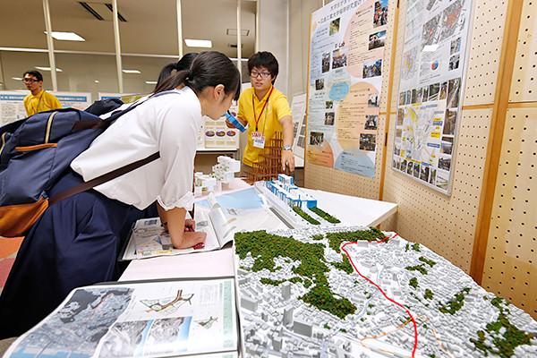 先輩の説明に聞き入る高校生。「設計ってどうやってやるの?」「模型づくりのコツは?」といった質問に、大学生は体験談や、建築分野のトレンドなどの情報を交えながら説明していました。(建築工学科)