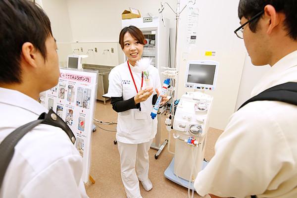 ケーシー服に身を包んだ先輩が、臨床工学技士の仕事の一つである人工透析の原理を説明。実際に透析器を組み立て、医療機器を工学的な視点から見ることで、その仕組みを理解することもできます。(生体医工学科)