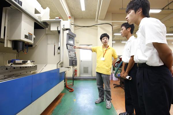 フライス加工、中ぐり加工、ねじ立てなどの異種加工を1台で行うことができる工作機械「立形マシニングセンタ」を見学。多数の切削工具を格納し、自動的に加工を行う機械にびっくり。(機械システム工学科)