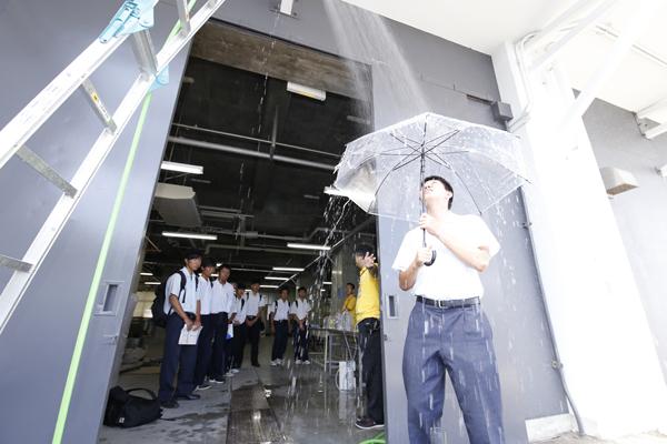 1時間250~300ミリの豪雨を体験。雨に押されて傘が沈み、雨音が大きすぎて他の音が聞こえなくなります。「防災を考える上で、データだけでなく感覚も大切です」という先生の言葉に、高校生は真剣に耳を傾けていました。(環境土木学科)