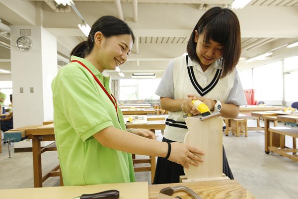 普段の授業で木材を加工し、家具等を作る際に利用する木工室では、糸ノコを使って板材を加工して、ミニメッセージボード作りを体験できました。難しいところは先輩学生がしっかりサポート。(建築デザイン学科)