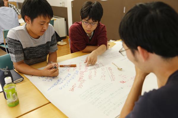 挙がった意見、気づいたことなどを、テーブルの上の模造紙に自由に書き込みます。ラウンドごとに、前のグループが書き込んだ意見を参考にしつつ話し合いを進めていきます。