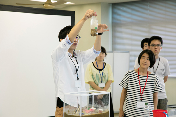 ペットボトルを使った液状化現象の実験も行いました。「ペットボトルの側面を指ではじいて振動を起こすと、砂の上のボールが沈みます。いっしょに作って、やってみよう!」