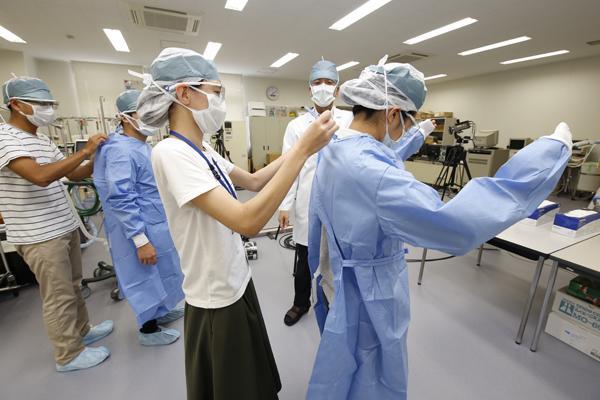 二人一組になって、手術用のガウンを着ていきます。袖を通す際も、両手を上にあげて清潔区域以外の箇所を触らないようにします。