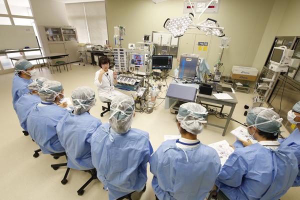 人工心肺装置の前で、機器の仕組みから名称、それぞれの働きなどの説明を聞きました。臨床工学技士を目指す本学の学生たちには馴染みのある機器ですが、他大学の学生にとっては、その仕組みを理解するための良い機会になりました。