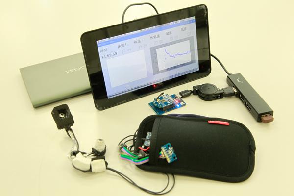 頸髄損傷者および介助者が常に体温を管理できる「体温モニタリングシステム」。画面の右側は耳と額で測った深部体温のグラフを、左側は外気温・気圧・湿度から計算した予測モデルの結果を色で表す計画です。