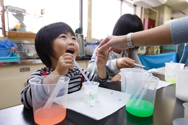 意外と難しいスポイトの使い方。実験器具の使い方や水溶液の作り方などを学生たちに教えてもらい、上手に落とせるようになると目が輝きます。