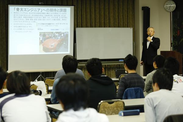 """「このゼミナールの一番重要な目的は人と人をつなぐことです。第2回となる今回のテーマは""""モノ""""。OB・OGの方と議論を深め、さまざまなつながりを作っていってください」と情報工学科の濱崎先生があいさつ。"""