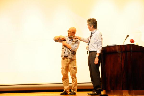 スマートフォンやメモ帳、ICレコーダーなどを装着した認知症患者向けのメモリーベストを披露する安田先生。