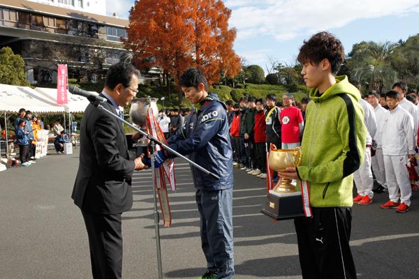 昨年、部活動の部で優勝した陸上競技部チームと、ゼミ・一般の部で優勝した地球環境学科チームによる優勝杯の返還。