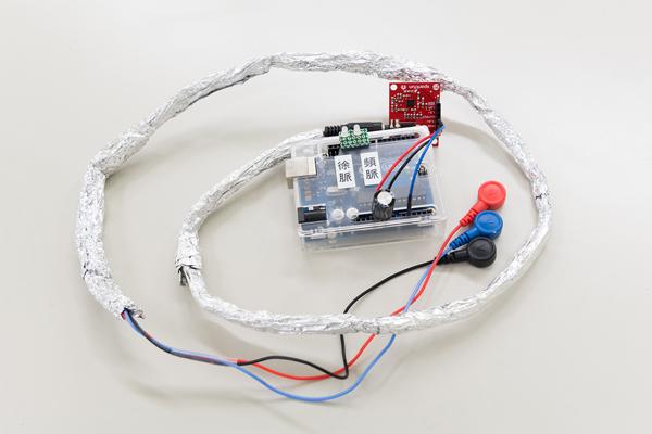 簡易型の心拍数検出システム。2つの電極を首の左右にあて、その間に生じる電位差から心拍数を測定します。不整脈が発生するとアラームで警告する仕組みです。