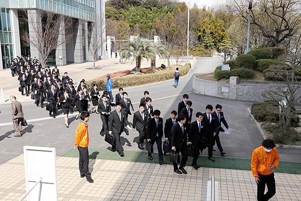 真新しいリクルートスーツに身を包んだ学生が、会場である鶴記念体育館に向かいます。