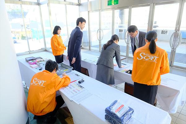 4年生は、オレンジ色のジャンパーを着て運営をサポート。出展企業の受付も行います