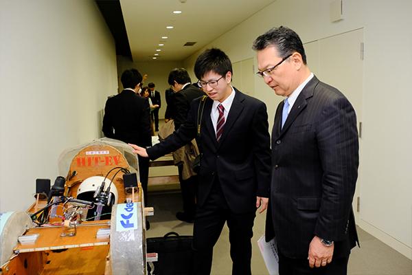 鶴学長にマシンを紹介するTeam HIT-EVの大西宏樹さん(知能機械工学科3年)