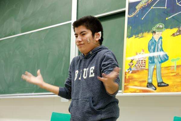 手話を披露する中原さん。背後の絵は、中原さんが宮沢賢治の世界をイメージして描きました。
