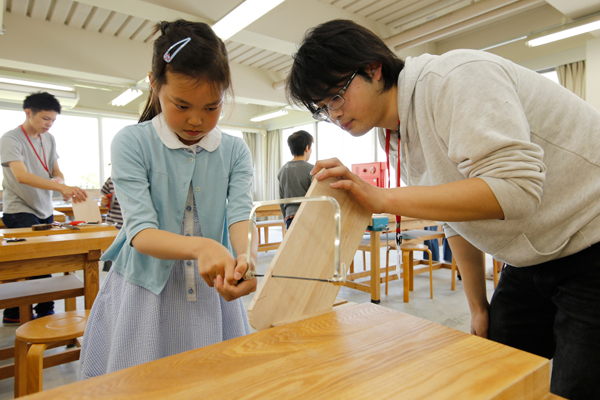 建築デザイン学科では、木工教室を開催。はじめての糸のこぎりに苦戦しつつも、学生の指導を受けながら、ミニメッセージボードを完成させていました。