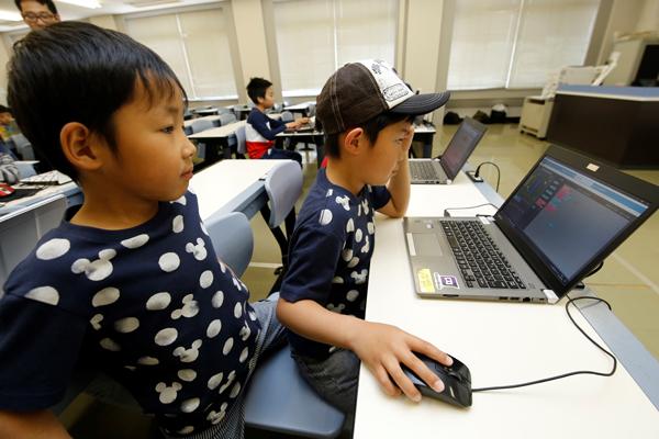 兄弟でゲーム作りに挑戦! パソコンに触るのが初めての参加者は、マウスの使い方から丁寧に教えています。