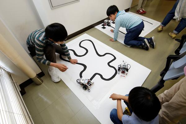 センサが黒い線をなぞりながら、ロボットカーが動いていきます。「上手く右に曲がらないから、プログラムの数値を変えてみよう!」ここでも挑戦が繰り返されていました。