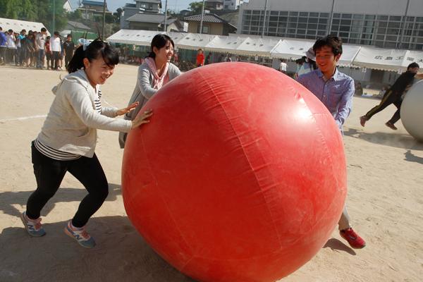3人で息を合わせて大きなボールを転がす「大玉転がし」。ボールに転がされないように、お互いに声を掛け合って進むことがポイント。
