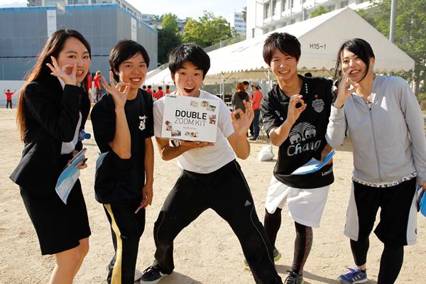リレーの優勝商品「一眼レフカメラ」をゲットしたのは地球環境学科4年の杉田さん(中央)。友人たちも祝福しました。