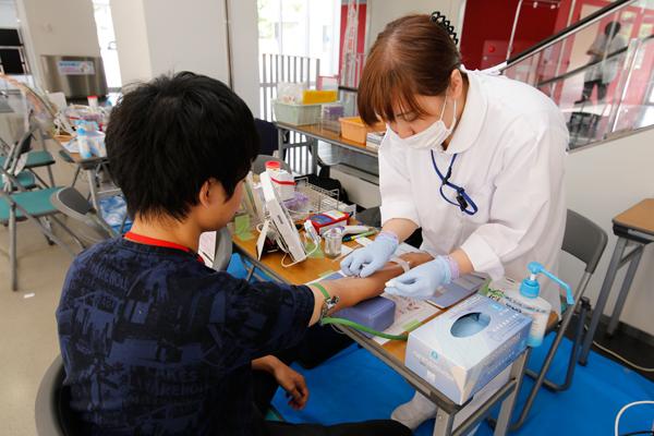 血圧や脈拍の測定、血液型判定や濃度測定を行います。いつも授業で利用している学び舎が、今日は病院のようです。
