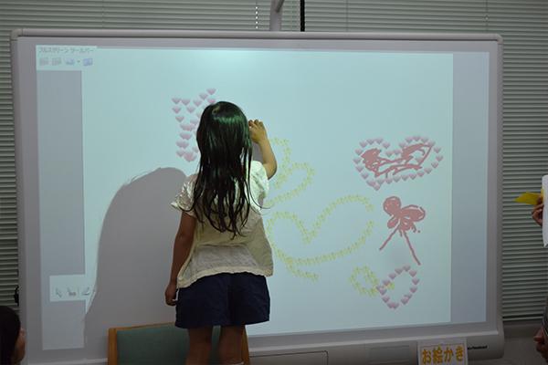 附属図書館で賑わっていたのは電子黒板を使ったお絵描きコーナー。指でタッチするとハートや星が出てくるスタンプ機能に、子どもたちは興味津々。
