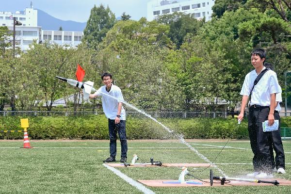 「高校対抗水ロケット大会」には、多くの高校が参加。水量や羽根の位置、発射角度など、先輩の大学生にアドバイスを受けながら工夫を凝らした高校生たち。青空の下、高く舞い上がる水しぶきに歓声を挙げていました。ちなみにこの日の最高記録は75mでした。