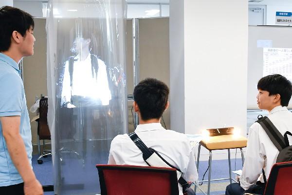写真の右側にいる高校生の映像が、左側の半円筒形・半透明スクリーンに投影されています。ネットワークさえつながっていれば、もっと遠く離れても同様に映像を投影するのが可能です。