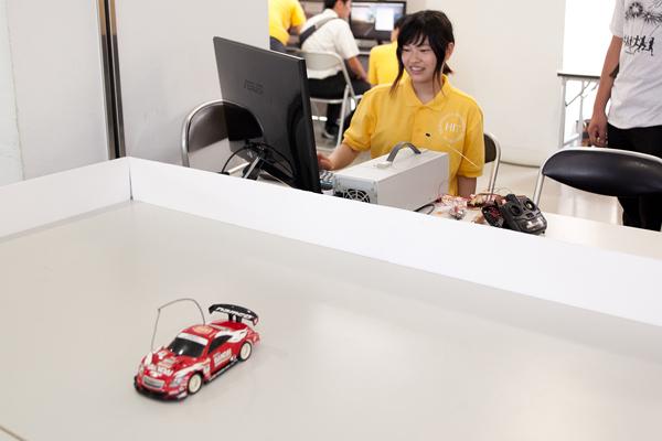 写真右にある黒いリモコンには一切触れることなく、赤いラジコンカーが走行を続けています。