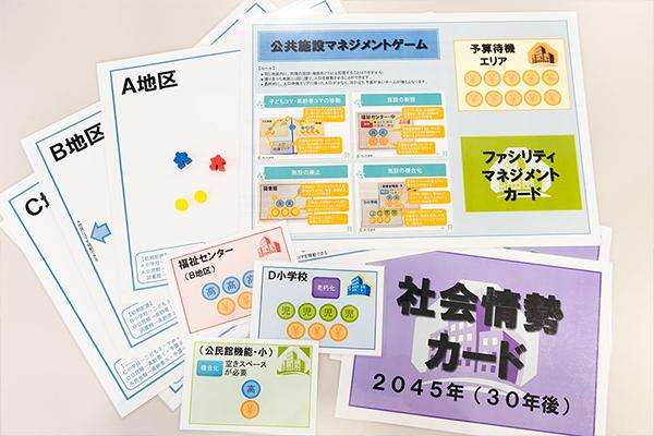 FMゲームに使用するアイテム。「A地区」「B地区」とエリアを示すカードもあれば、「福祉センター」「小学校」など施設を示すカードも。ひときわ大きい「社会情勢カード」には、「2045年(30年後)」などと書かれていますが...。