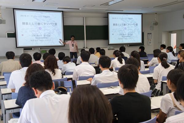 大学の講義を体験。これは食品生命科学科の「酵素として働くタンパク質」という講義。高校生は先生の話を聞きながら、大学生になった気分を味わいます。