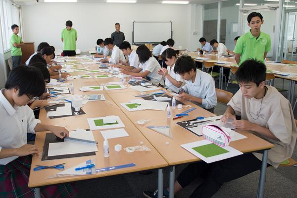 この写真は建築デザイン学科でのAO入試対策講座の様子。制限時間90分で、紙やテープなどを使って住宅の模型を組み立てる、という課題に高校生は、真剣そのもの。