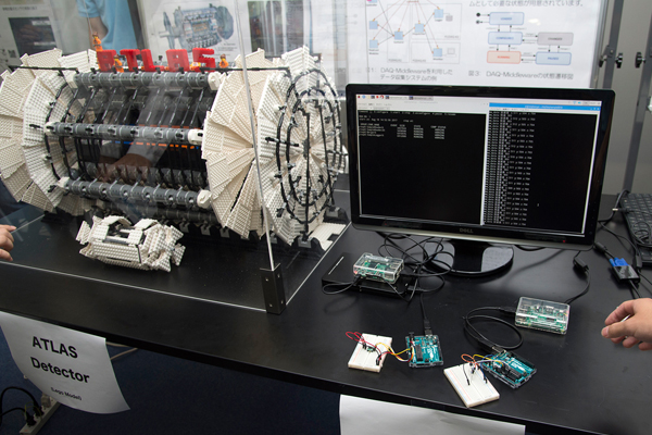 写真右下にある端末が、それぞれ加速度センサ、照度センサを取り付けたもの。写真左は、ATLASの模型をおもちゃのブロックで作ったもの。中にあるオレンジの人形が、人間サイズを表しています。ATLASとはこれほど巨大測定器なのです。
