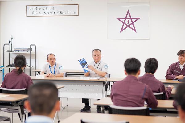 """はじめに古川製作所の井上執行役員から、会社についての説明と、同社が力を入れる""""カイゼン(改善)""""への思いを伺いました。「学生のみなさんの素直な視点から生まれる疑問をぜひぶつけてほしい。それを当社の""""カイゼン""""に生かしたい」という井上氏の熱い言葉に、学生たちは緊張の面もちながら、キャンパス内での講義とは違った気持ちの高まりを感じたようです。"""
